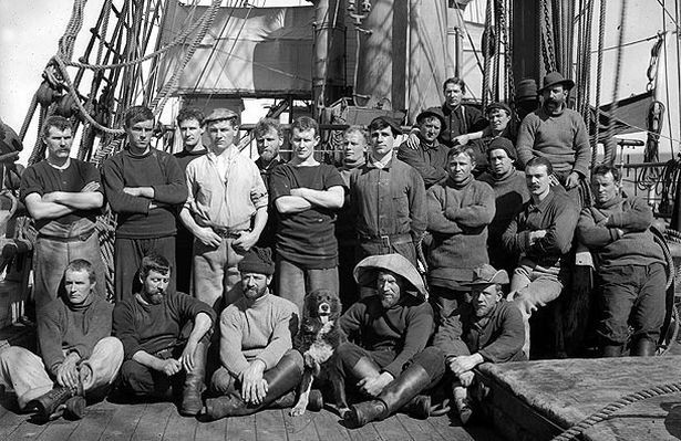 A group of men pose for a portrait on the deck of a ship