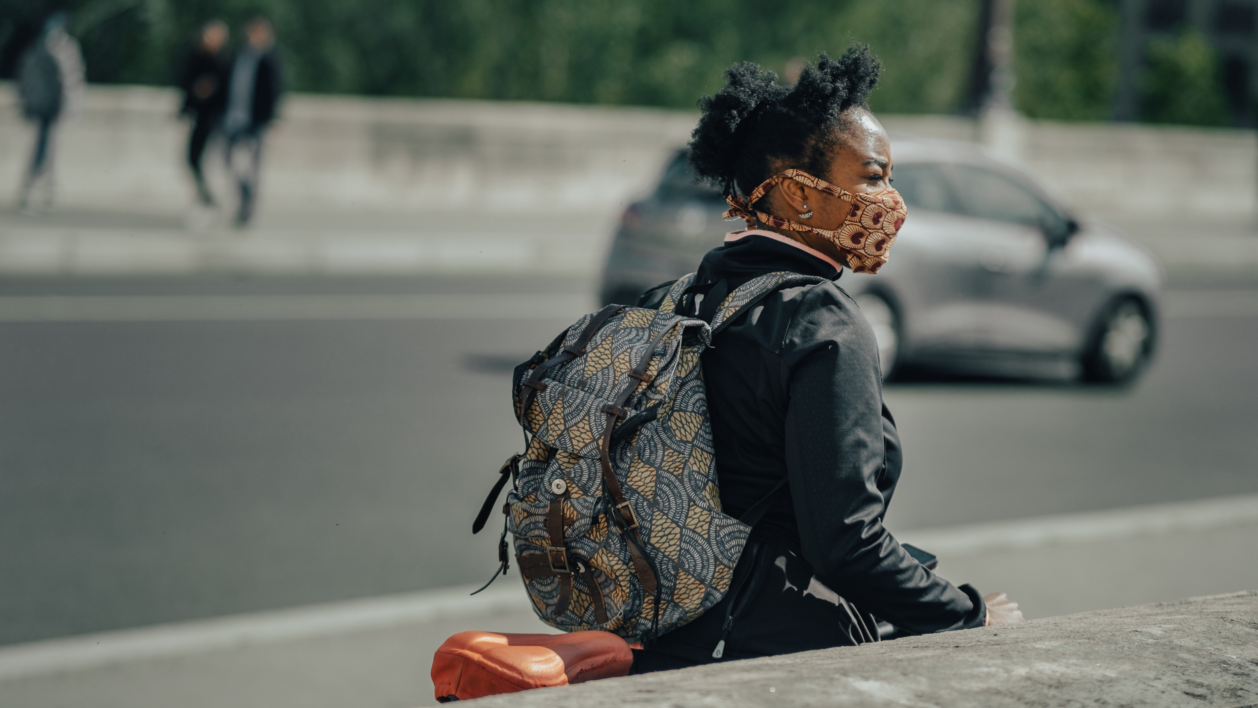 Young black woman walking in the streets with a bagpack and mask on.