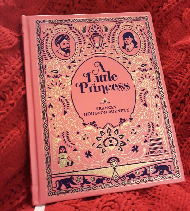 A pink hardback copy of A Little Princess with black and gold foil embossing.