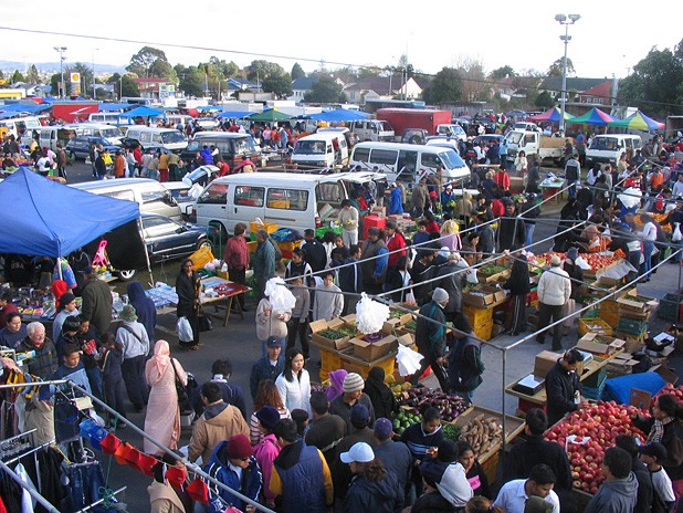 A busy market with lots of people, tents and vans