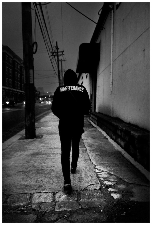"Man walking down the street, shoulders hunched, on his way to work. His jacket says ""Maintenance"" across the back."