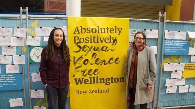 Laura and another person on two sides of a yellow banner saying 'Absolutely Positively Sexual Violence Free Wellington New Zealand'