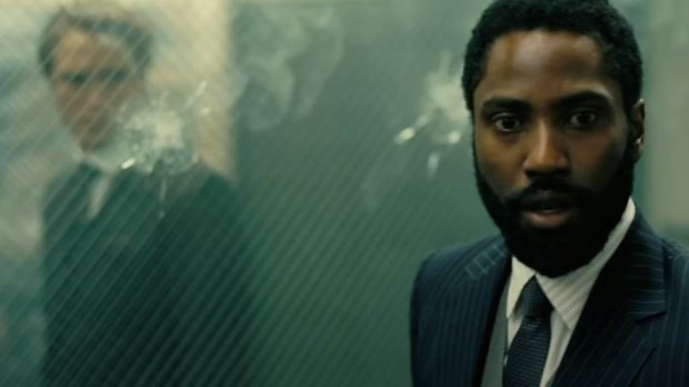 A blurred white man (left) & concerned bearded Black man (right) on either side of bullet mark ridden glass. Both wear suits.