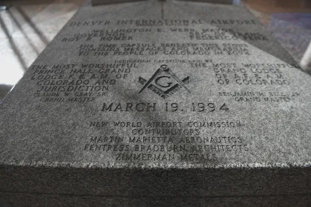 """A plaque from the Denver Airport. On it is carved the date """"March 19, 1994', a Masonic symbol, and a number of names and titles associated with the 'new world airport commission'."""