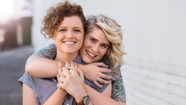 Brunette woman and blond woman hugging.