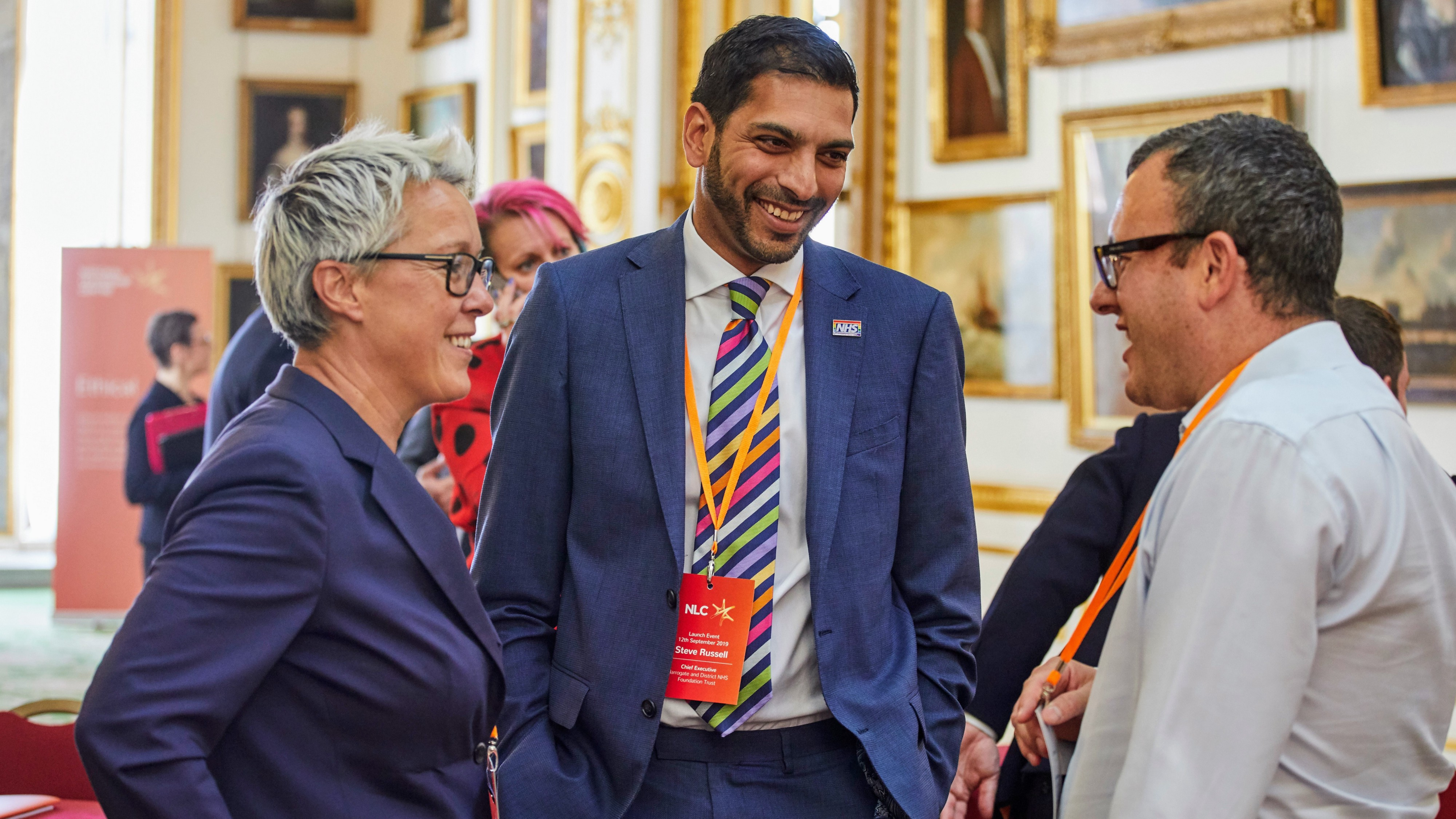 Three people laughing while talking at the National Leadership Centre's launch event