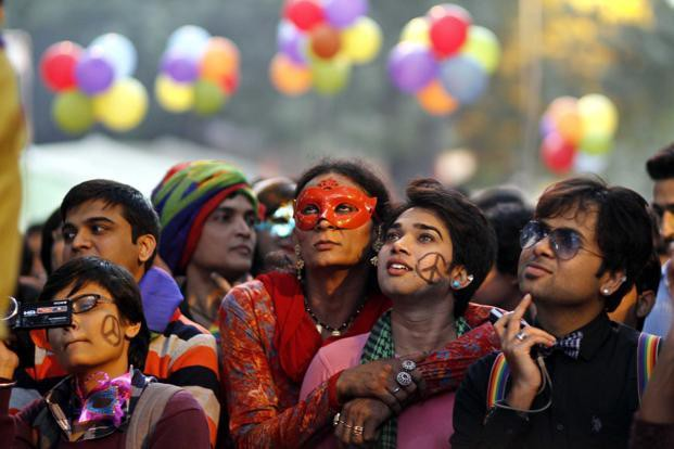 People from the LGBTQ community of India look up as balloons float in the background