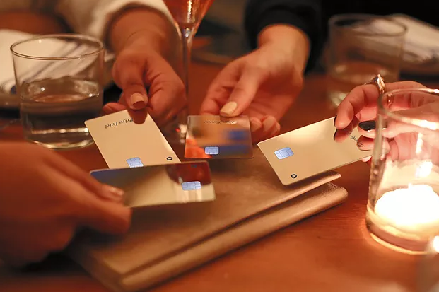 Four women putting their Sequin credit cards in the middle of a table