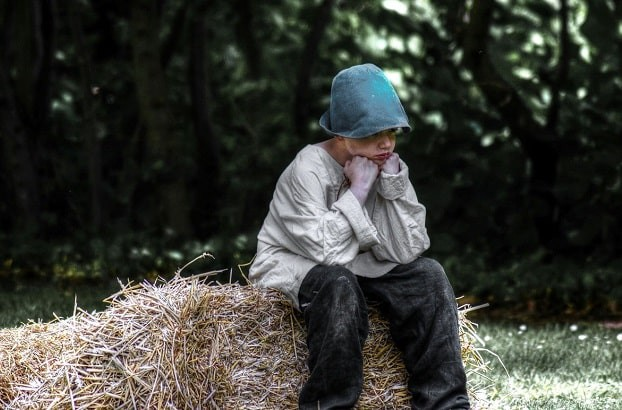 Boy sitting on bale of hay and pouting with head on fists.