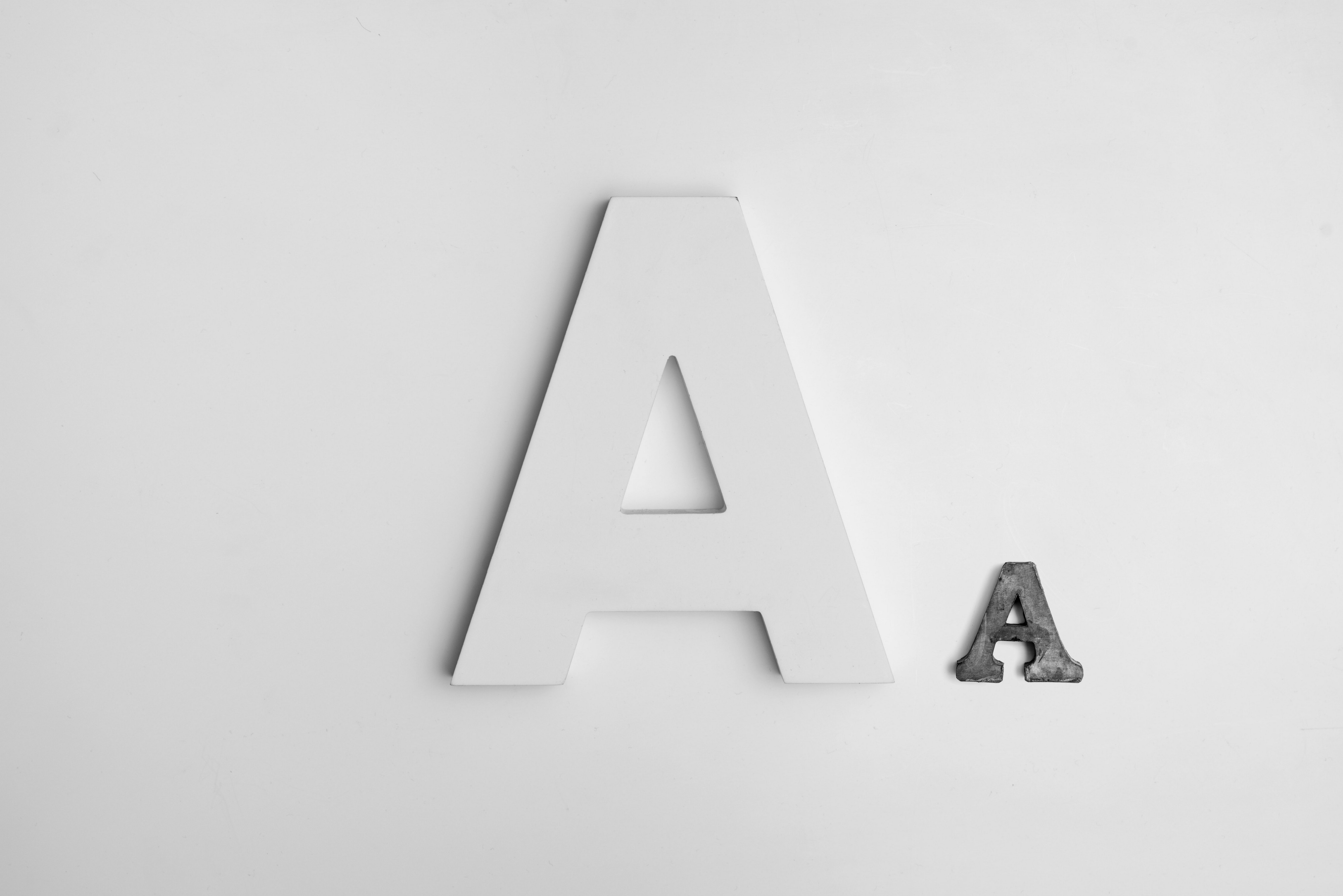 "A white, large, capital letter ""A"" next to a smaller, black, capital letter ""A""."