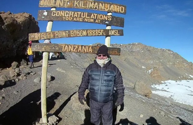 Solo picture of me standing in front of the sign for Stella Point on Mount Kilimanjaro.