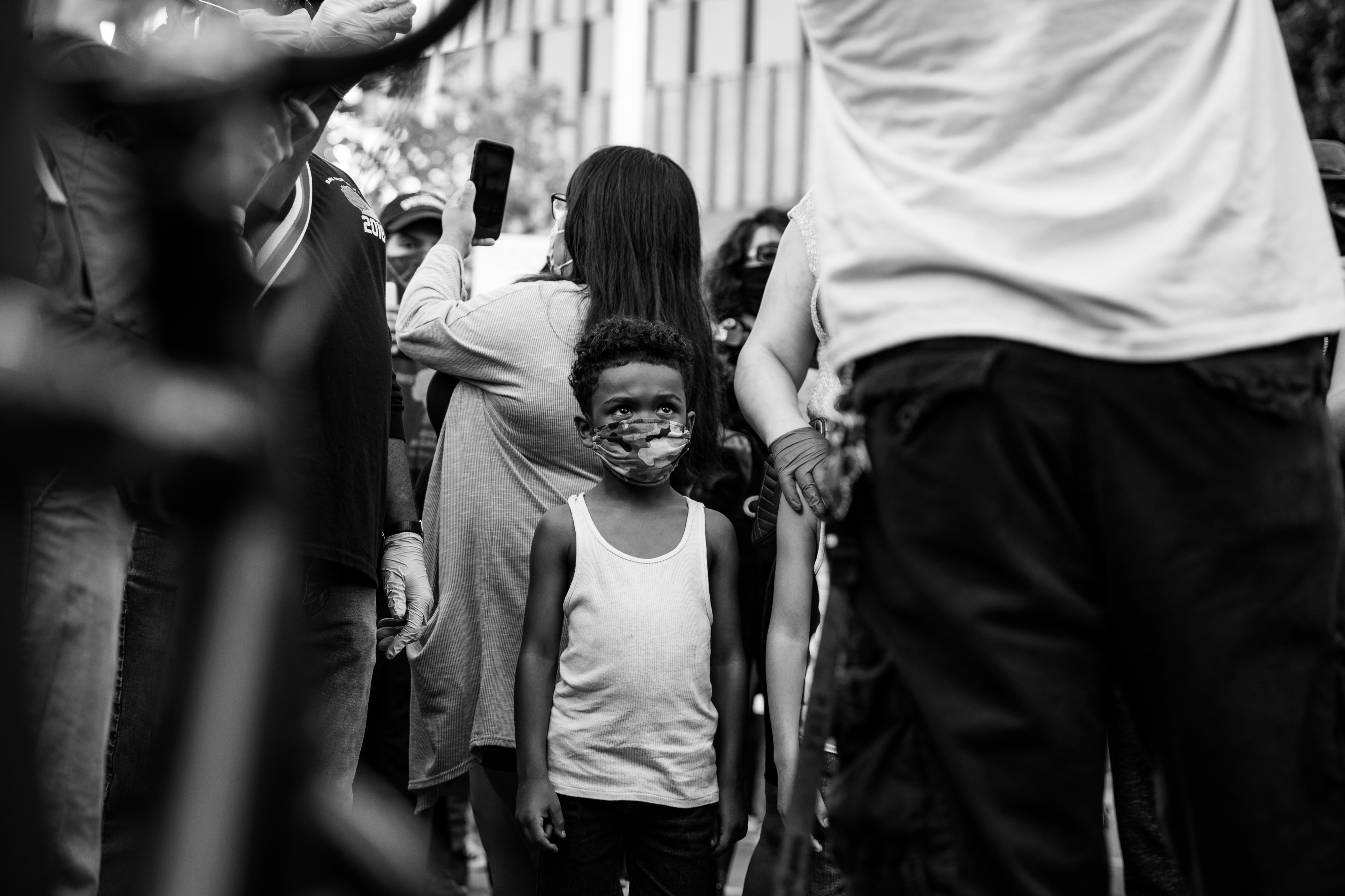 A black and white photo of a young Black boy wearing a face mask at a protest in LA.