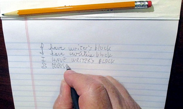"""Hand with pencil and pad writing """"I have writer's block"""" over and over"""