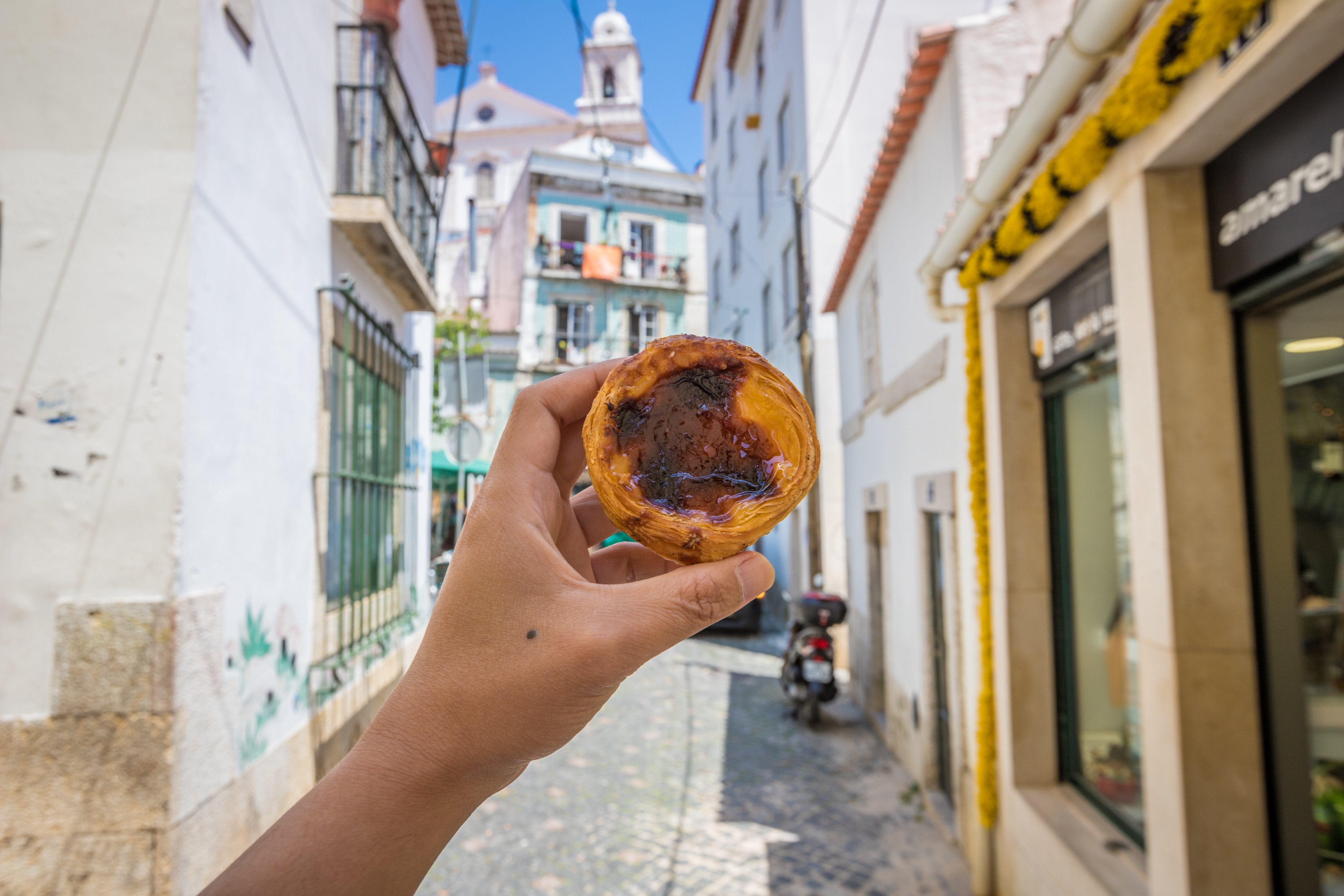 Hand holding Portuguese custard pastry in front of typical Lisbon backdrop.
