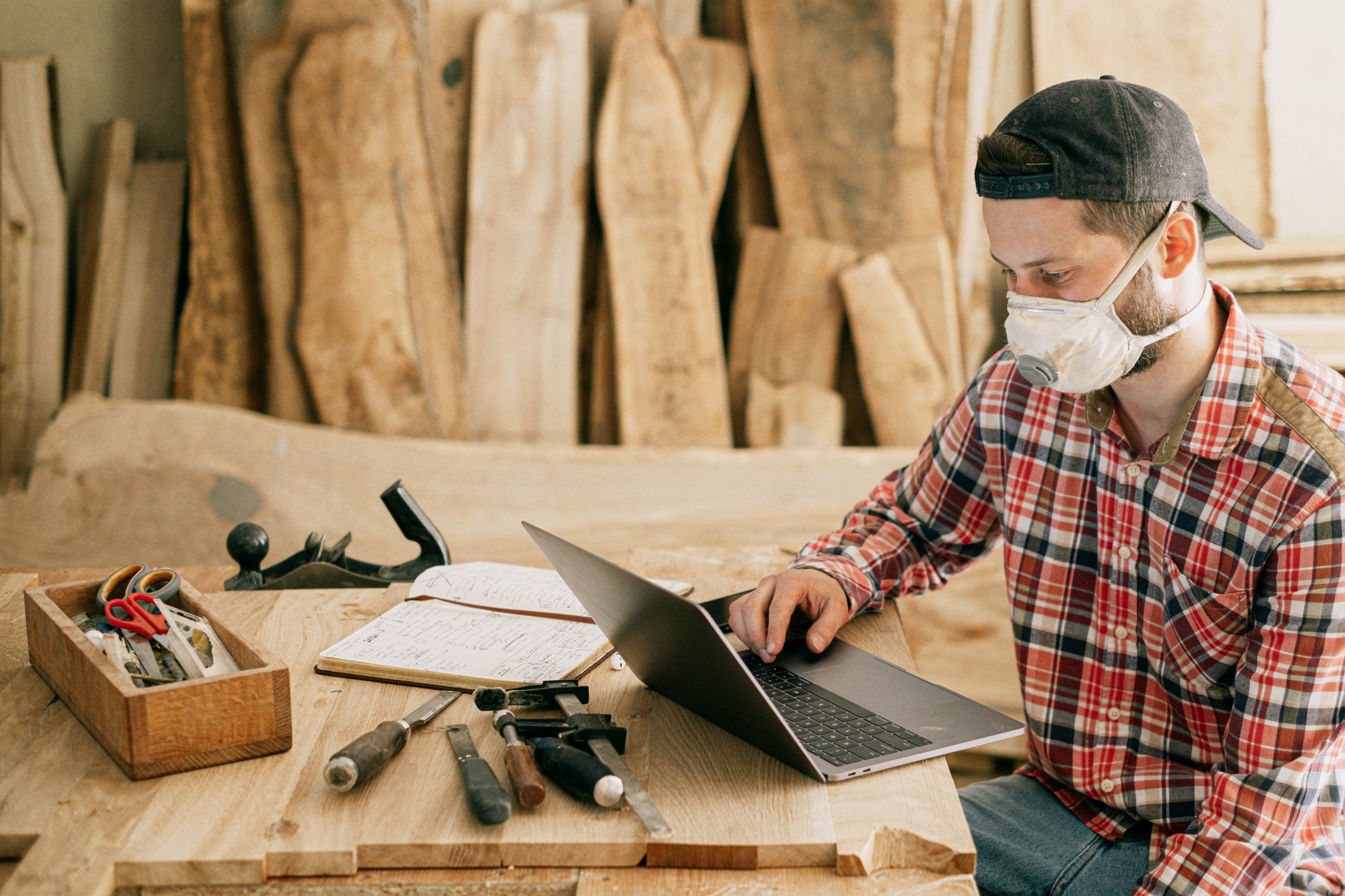 Carpenter working on his laptop surrounded by wood