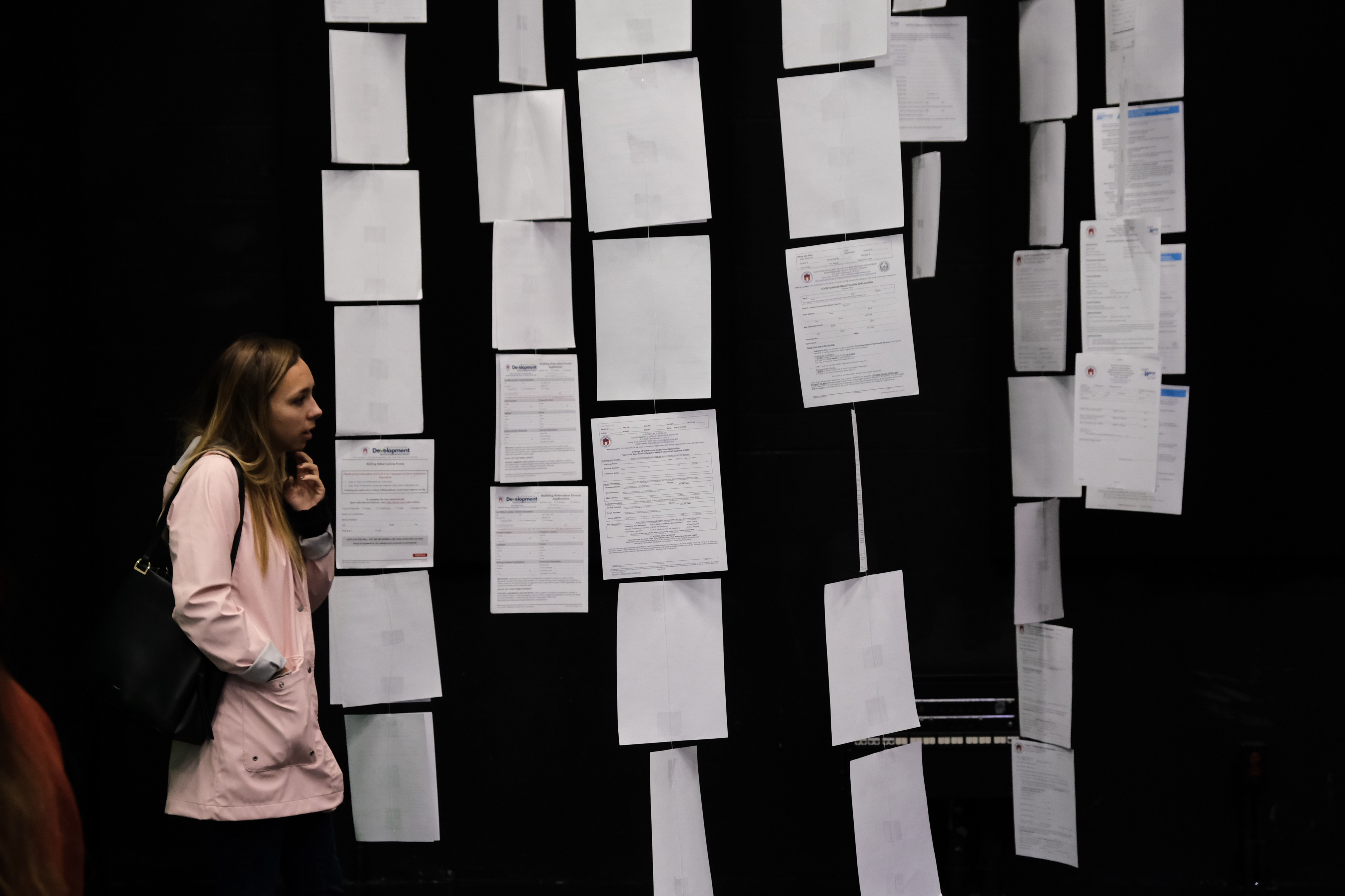 A women in a pink sweater looks at a row of forms along the back wall.