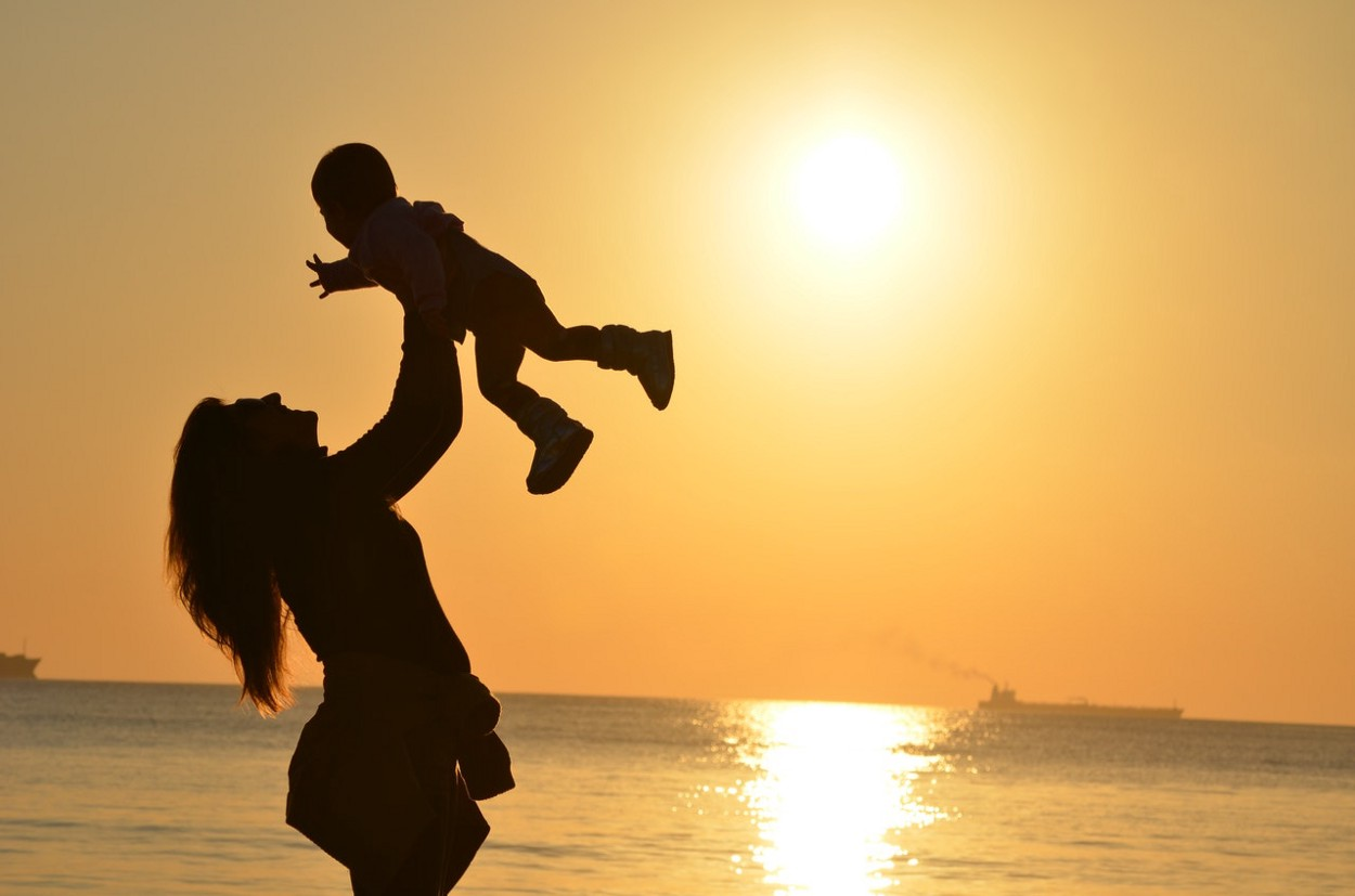 Mom tossing child with sunset as backdrop