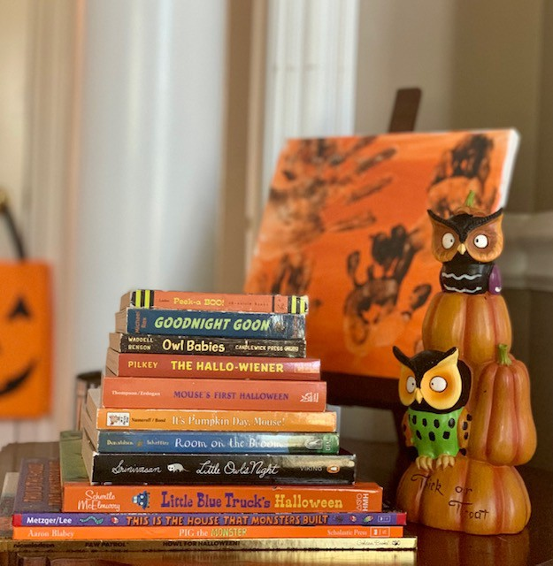Stack of children's Halloween books with owls figurine to the right and an orange canvas with brown handprints in the background.