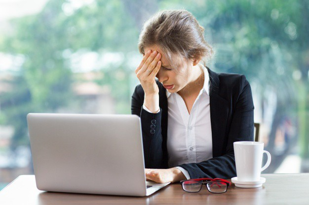 Woman with a headache sitting at a computer