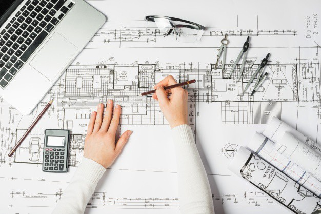 Architect's hands drafting a floor plan over a a large sheet of paper on a desk.