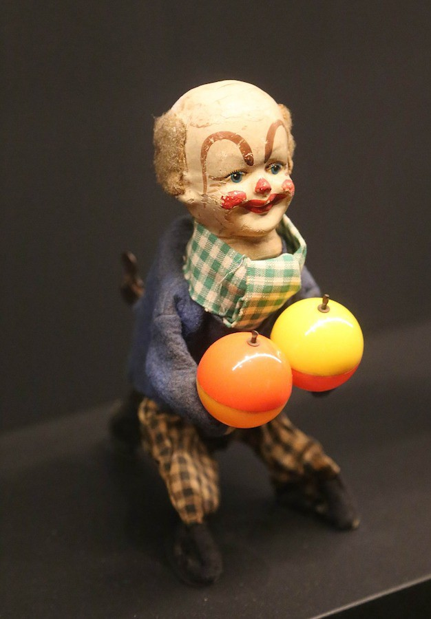 A small wind-up toy clown clutches two balls, one orange and one yellow.