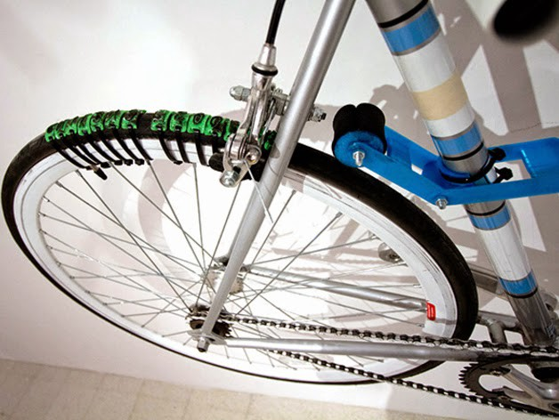 riottech: bike tyre with strapped on letter stamps forming the words