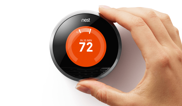 A hand adjusting the nest thermostat to warm up to 72 degrees.