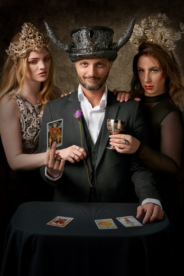 Magician and two women holding tarot cards
