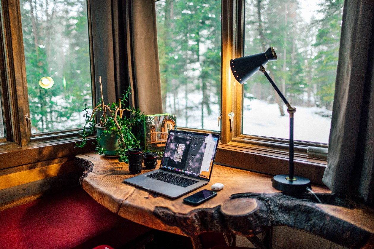 A cozy and rustic built-in desk made out of wood. There is a lamp shining on the laptop and two windows overlooking a forest.