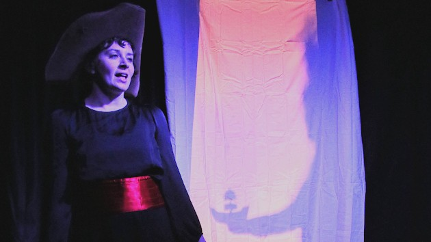 An actress in outlandish costume standing in front of a shadow puppet screen
