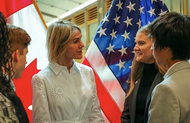 New USUN ambassador Kelly Knight Craft speaks with teenagers in front of US and Canadian flags