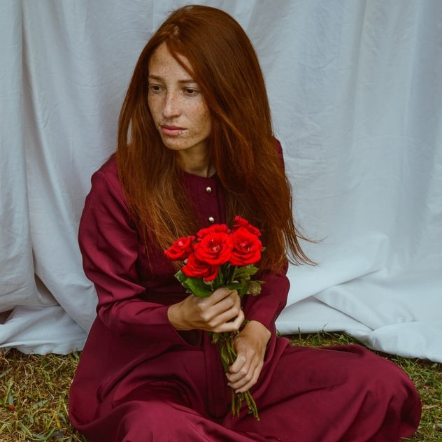 A red-haired girl in a red dress holds a bunch of red roses