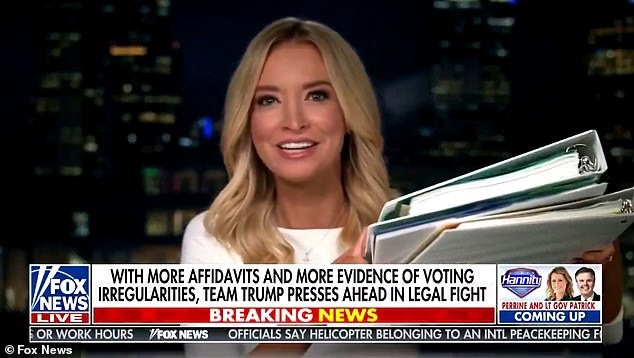 Kayleigh McEnany wears a white shirt & holds white binders whitely on Fox News