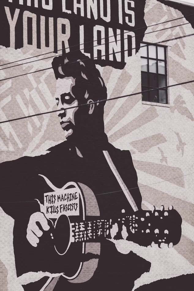 """Mural of Woody Guthrie holding a guitar that says, """"This machine kills fascists."""""""