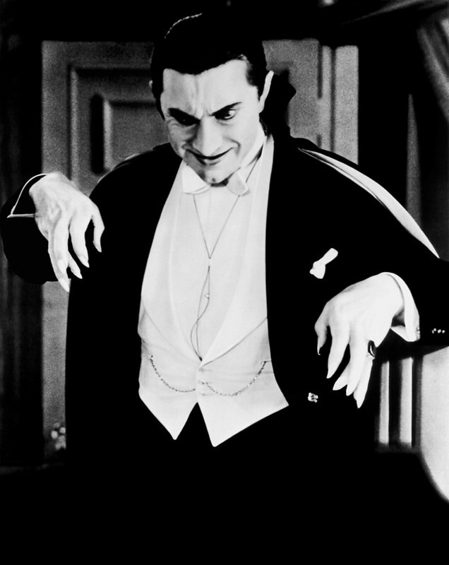 An actor portraying a vampire raises his hands and smiles