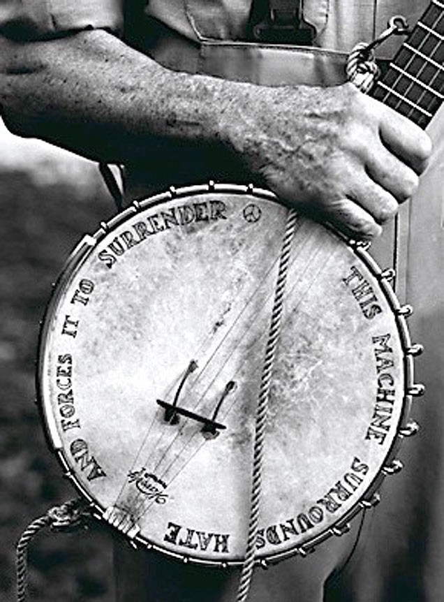 "Pete Seeger's banjo says ""The Machine Surrounds hate and Forces it to Surrender."""