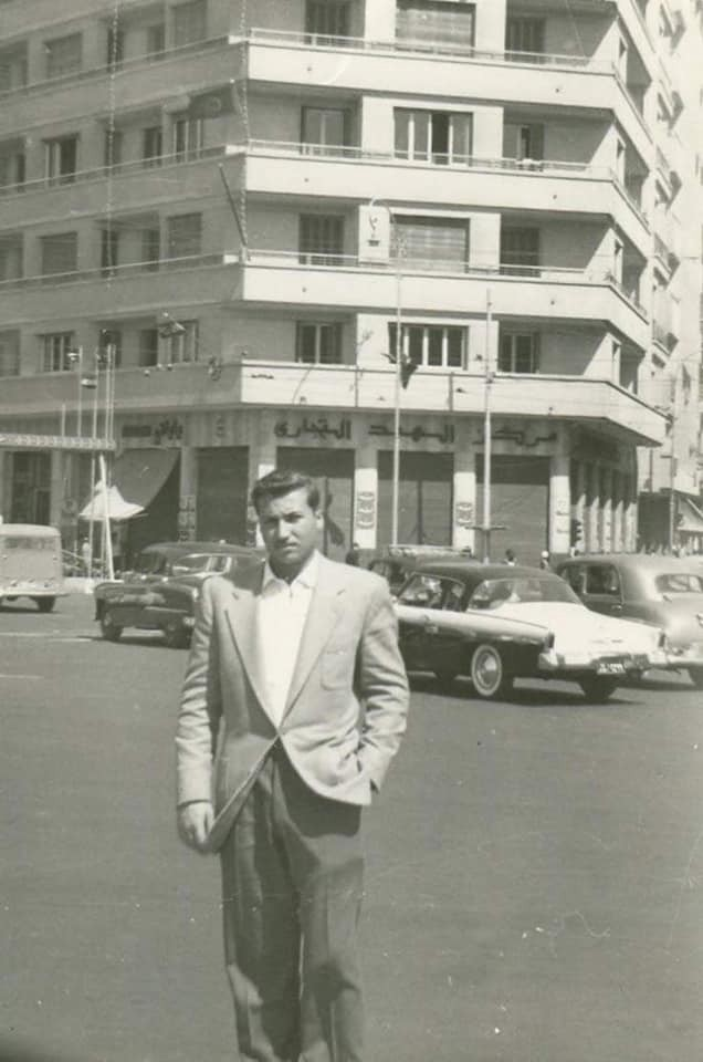 Black and white photo of my father from the 1960s in Cairo, Egypt. He is dressed in a suit standing in a busy street.