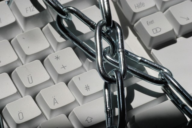 Image shows a keyboard wrapped in metal chains