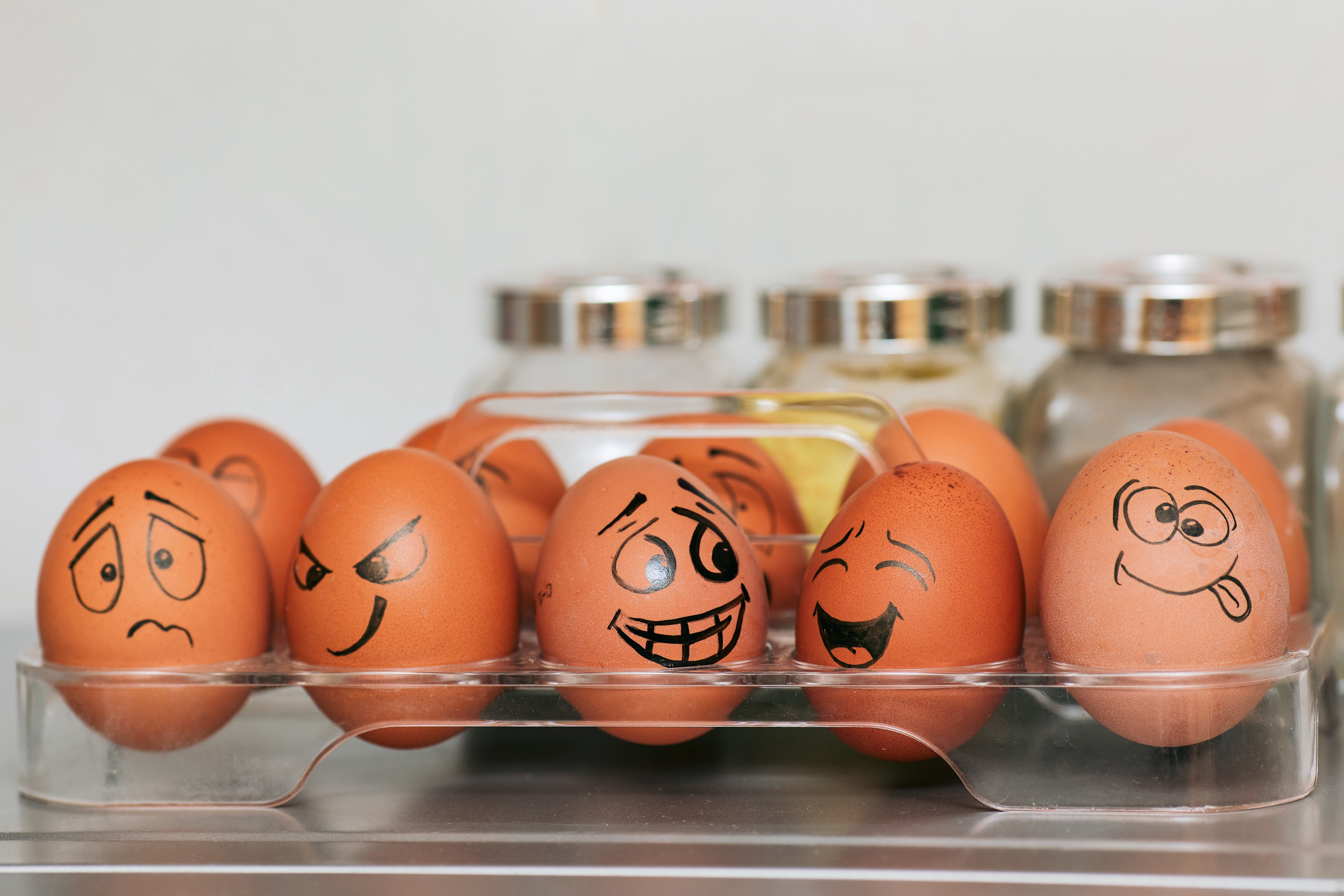 Brown eggs in a container with faces drawn onto them expressing emotions: sadness, confidence, mirth, silliness, etc.