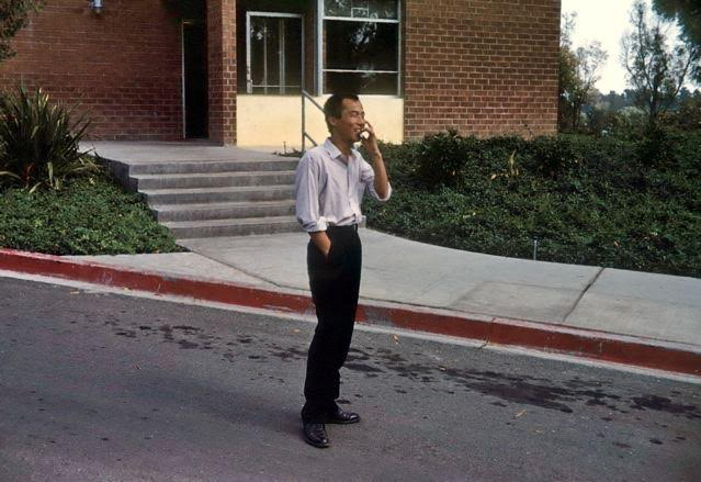 My father, a slender Korean man standing on a street in front of a brick building, smoking a cigarette. He's wearing a white button down shirt and black slacks, black leather shoes, smiling at someone or something in the distance off camera.