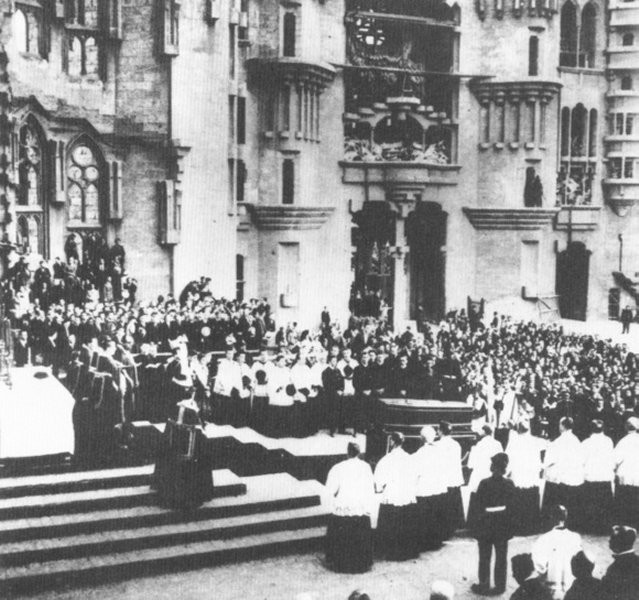 A grainy black and white photo of a crowded funeral procession.