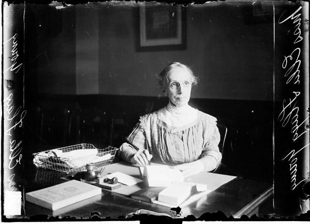 Ella Flagg Young seated at her desk.