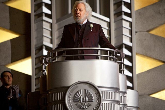 Screenshot from The Hunger Games movie. President Snow addresses the tributes from a silver podium.