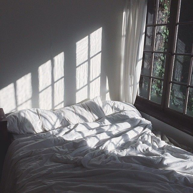 Sunlight streaming in the window, casting shadows on an unmade bed with white sheets.