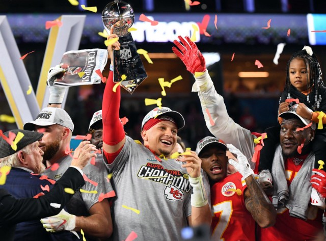 Super Bowl 54, Kansas City Chiefs victory celebration, Patrick Mahomes holding up the Lombardi trophy surrounded by teammates