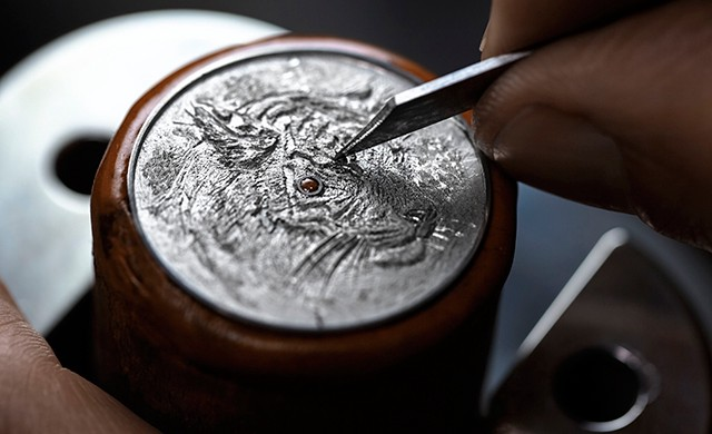 Engraver Olivier Vaucher working on what will eventually become the dial of the Hermès Arceau Tigre