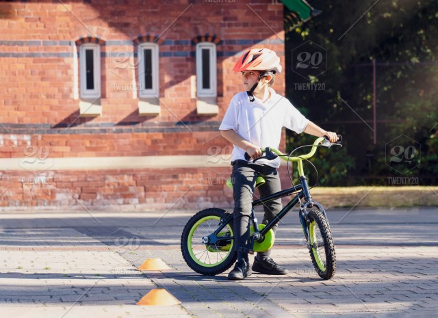 Little boy with a helmet at a playground on his bike
