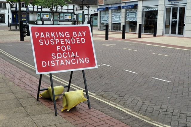 A red roadwork sign in a parking space that says 'parking bay suspended for social distancing'