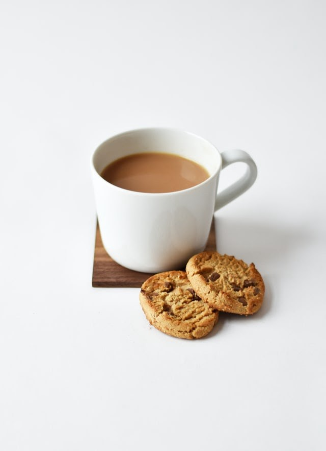 A white mug of hot chocolate on a wooden coaster with two chocolate chip cookies beside it.