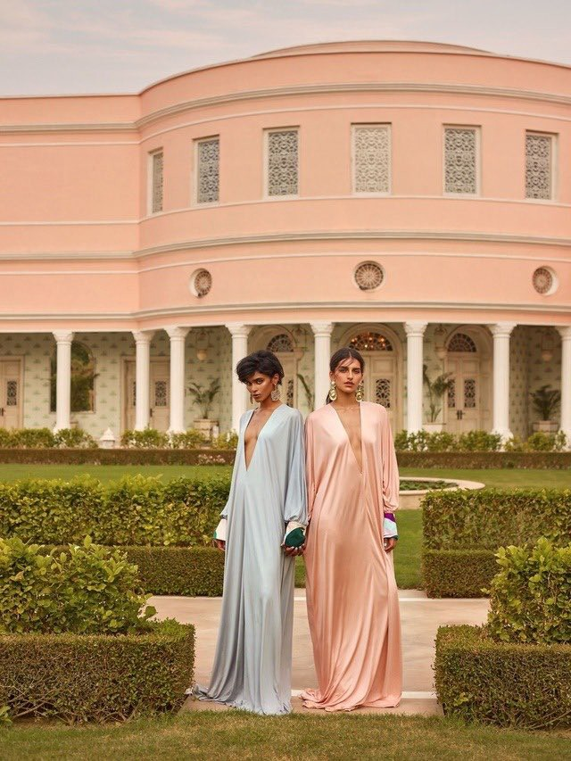 Models in pastel silk gowns in front of a courtyard